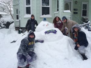adulchildren build a giant snowman
